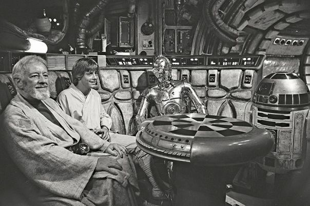 Sir Alec Guinness, Mark Hamill, Anthony Daniels and Kenny Baker sit at the Millennium Falcon game table